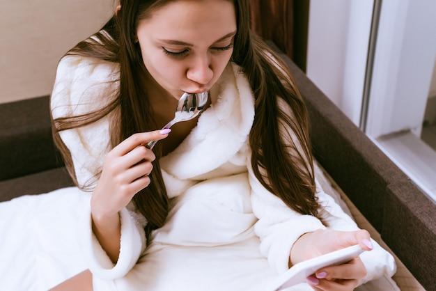 白いローブを着たかわいい若い女の子が早く目を覚まし、ベッドに座って朝食をとり、スマートフォンをのぞき込む