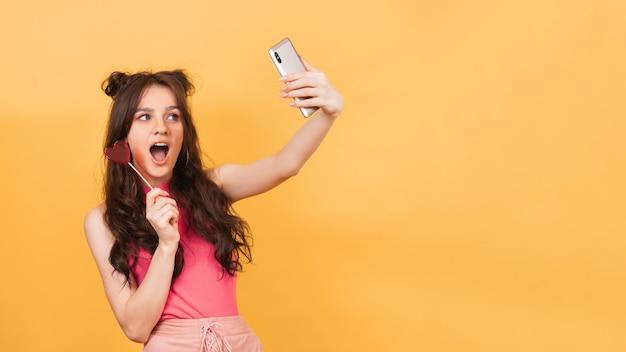 ピンクのかわいい女の子がハート型のロリポップを手に持ち、笑顔でスマートフォンで自撮りをしている。あなたのテキストのための場所