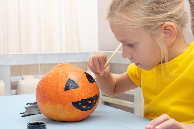 かわいい若い女の子は、ハロウィーンの休暇中に家を飾るためにブラシでオレンジ色のカボチャに怖い顔を描いています。ハロウィーンパーティーと家族のライフスタイル