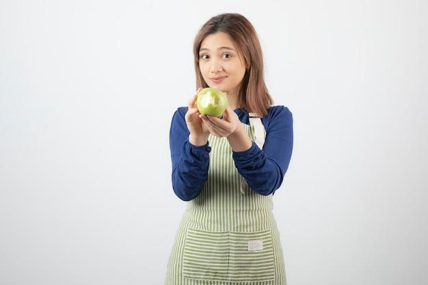 Милая молодая девушка модель в фартуке держит зеленое свежее яблоко.