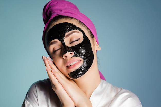かわいい若い女の子は眠りたいです、彼女の目は閉じています、彼女の顔はにきびに対する黒いマスクです