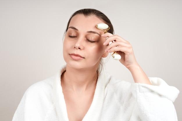 白いローブを着たかわいい若い女性は、翡翠のロールを使用して顔をマッサージし、目を閉じます