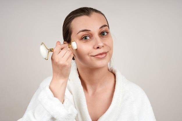 白いローブを着たかわいい若い女性は、翡翠のロールを使用して顔をマッサージします
