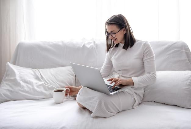 귀여운 젊은 여자가 집에서 흰 드레스에 흰색 소파에 앉아 일하고 있습니다. 원격 작업 및 프리랜서 개념.