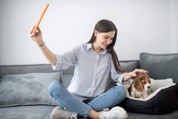 子犬と一緒に自分撮りをして幸せそうに見えるかわいい若い女性