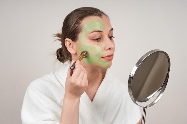 かわいい若い女性が彼女の顔に緑色のマスクを置き、鏡を見ます。