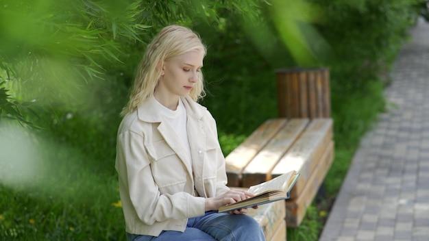 かわいい若い女性が公園のベンチに座って、のんびりと本を読みます。野外レクリエーション。 4k uhd
