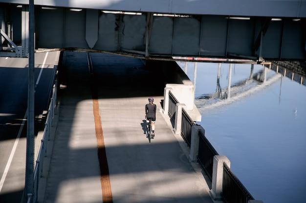 Освещенный солнцем велосипедист едет по набережной