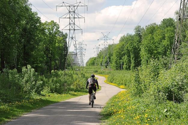 サイクリストが電力線の間の道路に乗る