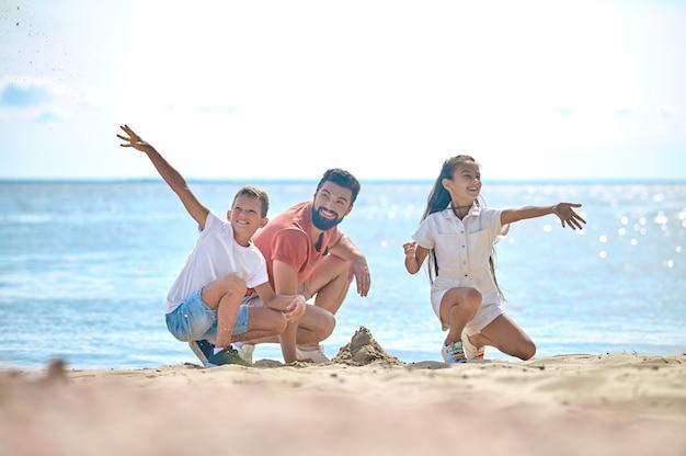 Папа с детьми строят замки из песка