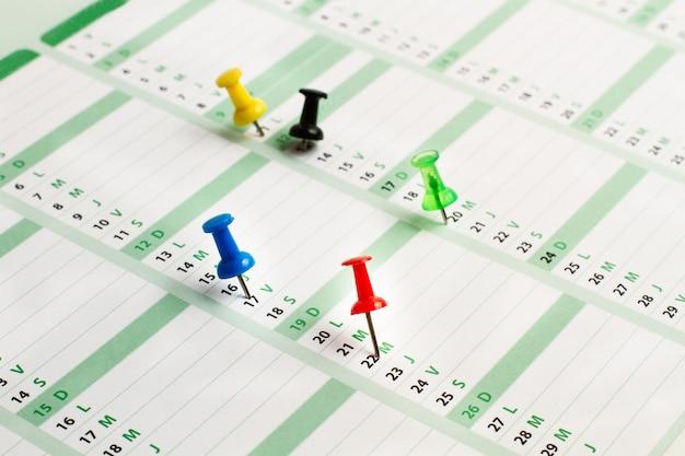 いくつかの日をマークする色付きの画鋲が付いた日カレンダー