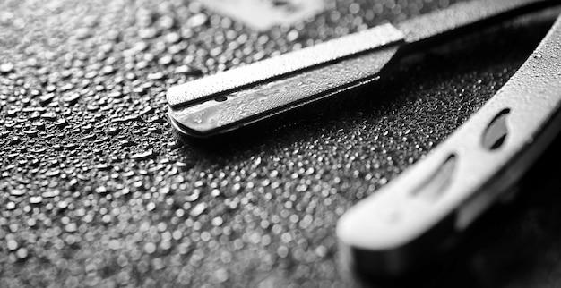 危険なかみそりとテーブルの上の金属の刃。メンズシェービングアクセサリー。本物の男性のための残忍なシェーバー。テーブルの上の水滴。