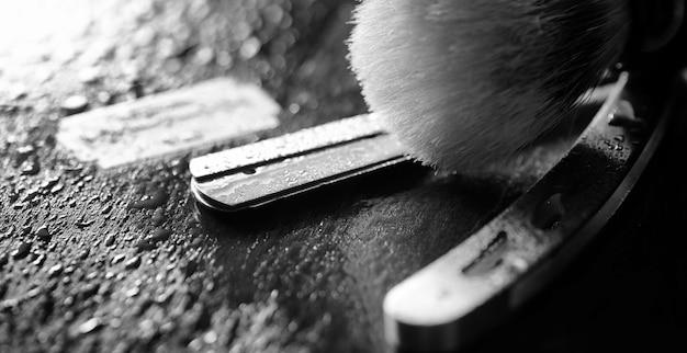 危険なかみそりとテーブルの上の金属の刃。メンズシェービングアクセサリー。本物の男性のための残忍なシェーバー。テーブルの上の水滴。 Premium写真