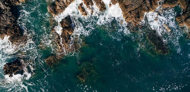 嵐の前に危険な海の波がスプレーと泡で岩の多い海岸に衝突します