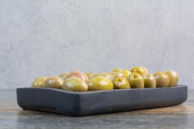 Темная доска соленых вкусных оливок на мраморном фоне. фото высокого качества