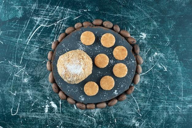カラフルな背景にケーキとクッキーの暗いボード。高品質の写真