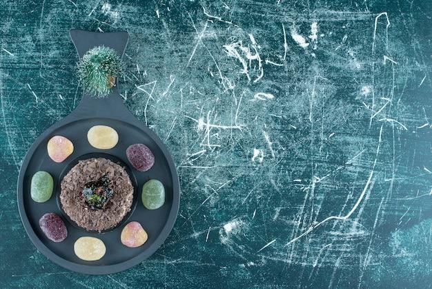 Темная доска с шоколадным тортом со сладким мармеладом. фото высокого качества