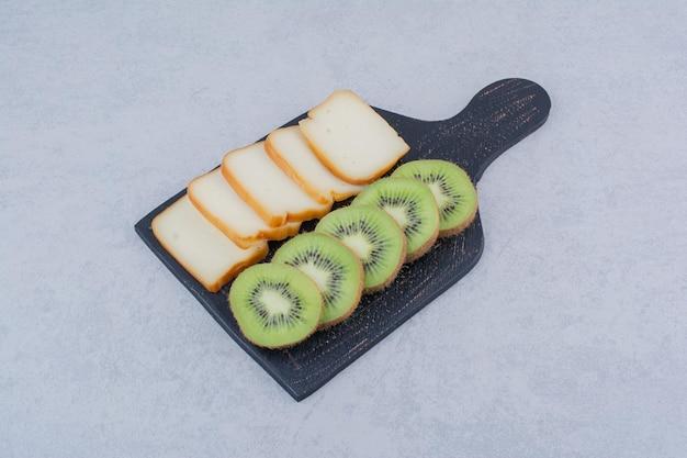 Темная доска с нарезанным хлебом и свежим киви. фото высокого качества