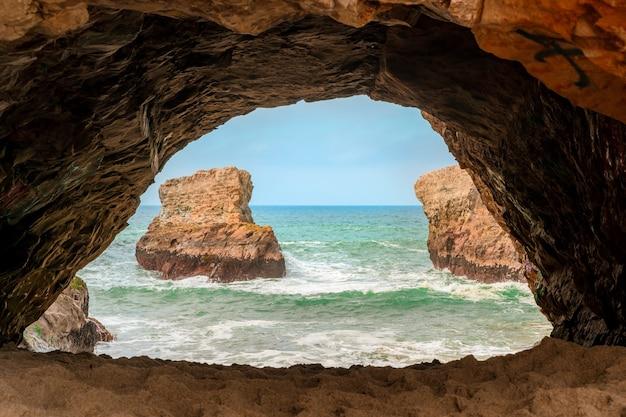 太平洋の波とカリフォルニアの岩の美しい景色を望む暗い洞窟