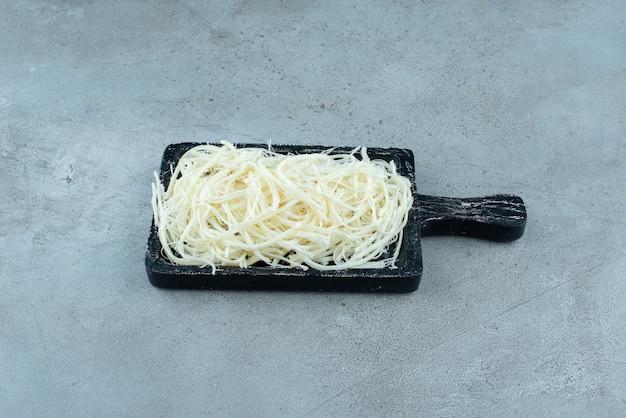 파란색 배경에 치즈가 가득한 어두운 커팅 보드. 고품질 사진