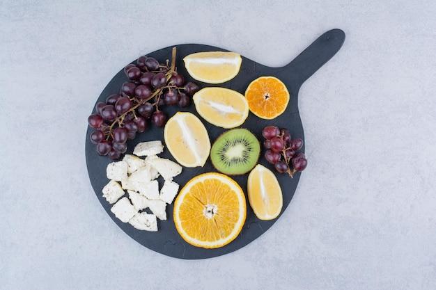 신선한 달콤한 과일과 슬라이스 화이트 치즈의 어두운 커팅 보드. 고품질 사진