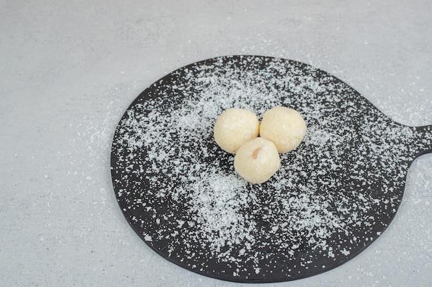 가루 설탕을 넣은 둥근 페이스트리를 넣은 어두운 도마