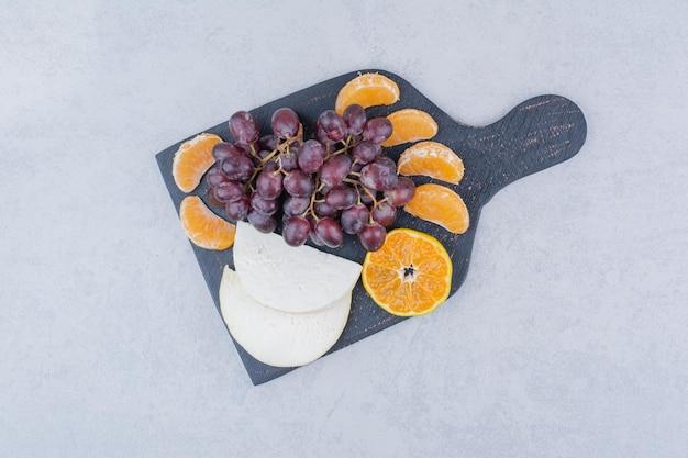 Темная разделочная доска с нарезанным сыром и фруктами. фото высокого качества