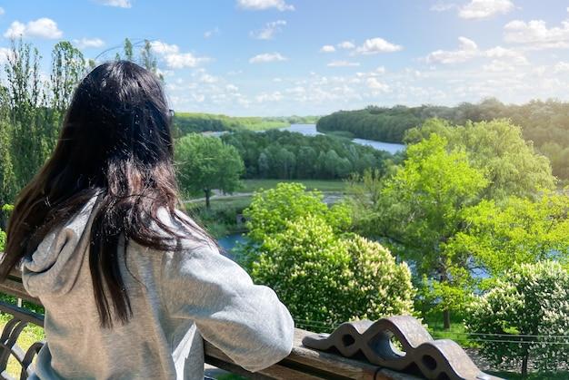 黒髪の白人の女の子は、明るい灰色のジャケットを着て背中を向けて立っており、ウクライナのチェルニヒウ市の川と森の方を向いています。