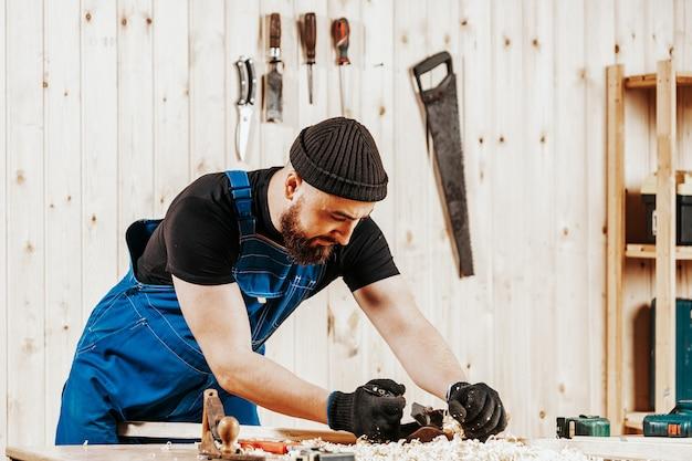ひげと黒のジャックプレーンで木の棒を扱うオーバーオールの黒髪の男