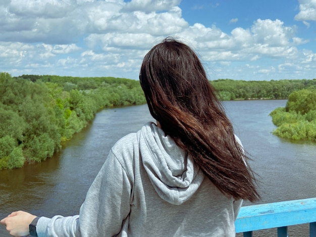 黒髪のñ白人の女の子は、明るい灰色のジャケットを着て背中を向けて立っており、ウクライナのチェルニゴフ市の川と森の方を向いています。