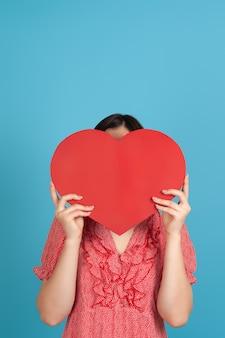 Темноволосая женщина в красном платье прячет лицо за большим красным бумажным сердцем
