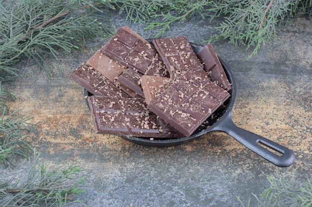 Темная сковорода, полная нарезанных шоколадных конфет на мраморном фоне. фото высокого качества