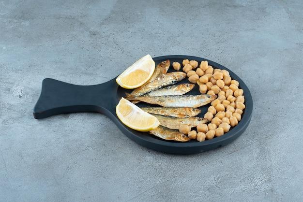 회색 배경에 생선과 완두콩이 있는 어두운 팬. 고품질 사진