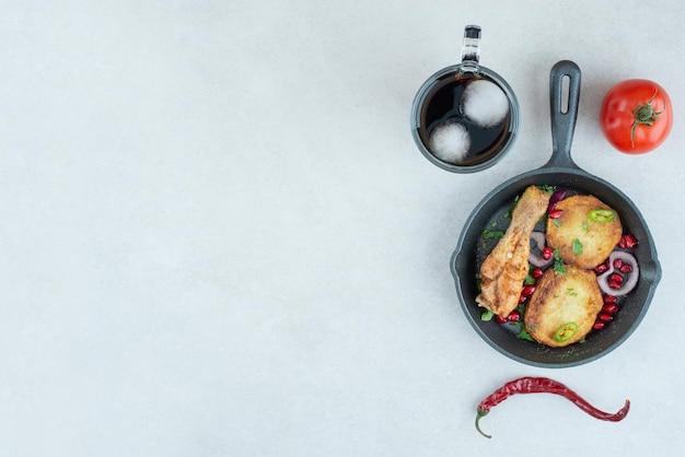 Темная сковорода с жареной курицей и картофелем на белом столе.