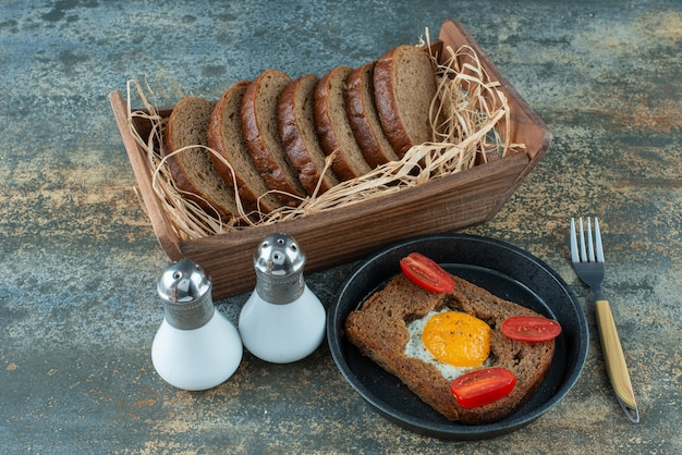 大理石の背景に目玉焼きと茶色のパンのスライスと暗い鍋