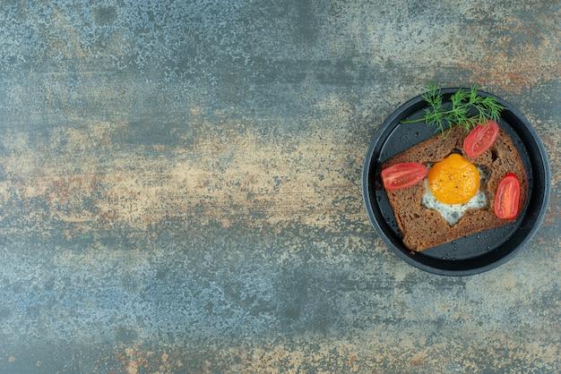 大理石の背景に目玉焼きとトマトの暗い鍋