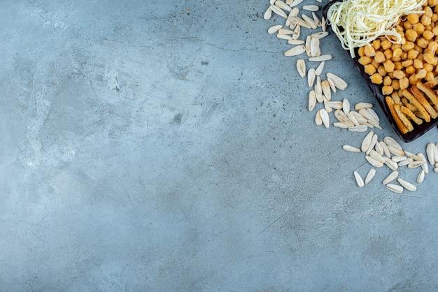 회색 배경에 치즈와 완두콩으로 가득 찬 어두운 접시. 고품질 사진