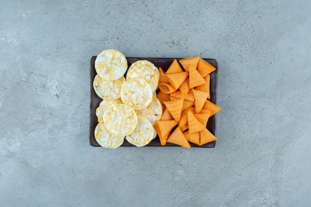 회색 배경에 바삭한 칩으로 가득 찬 어두운 접시. 고품질 사진
