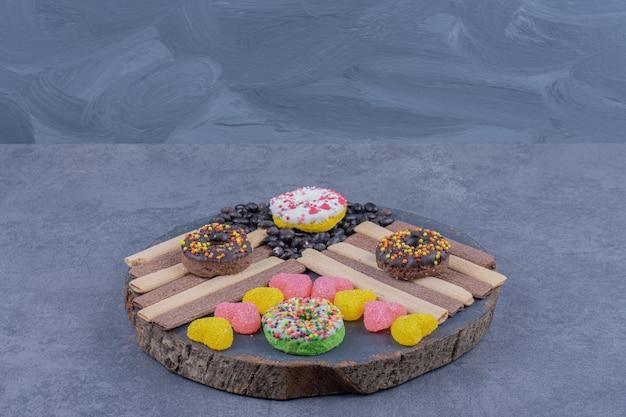 Темная тарелка, полная пончиков и желейных конфет в форме сердца
