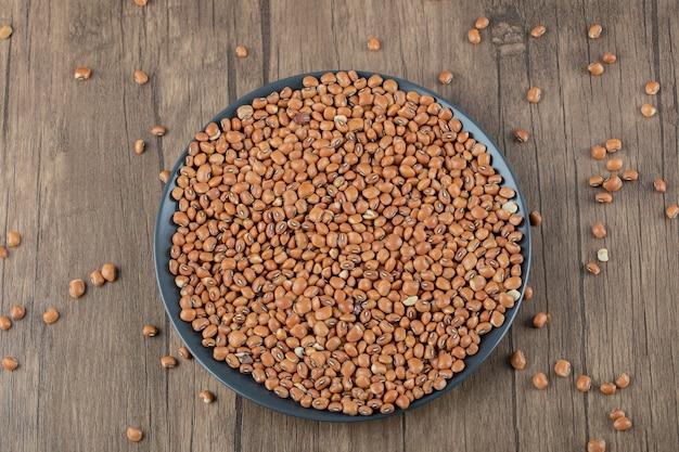 乾燥した生の小豆でいっぱいの暗いプレート