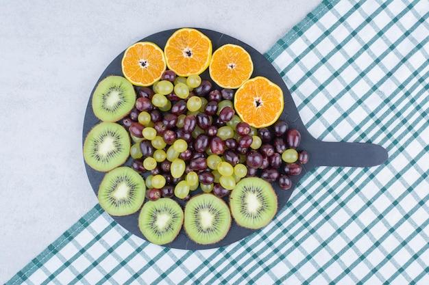 テーブルクロスの上にブドウ、キウイ、オレンジでいっぱいの暗いプレート。高品質の写真