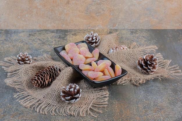 Темная тарелка с мармеладом в форме сердца и шишками. фото высокого качества