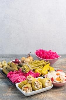 Темная тарелка, полная маринованных огурцов и красной соленой капусты на мраморном фоне. фото высокого качества
