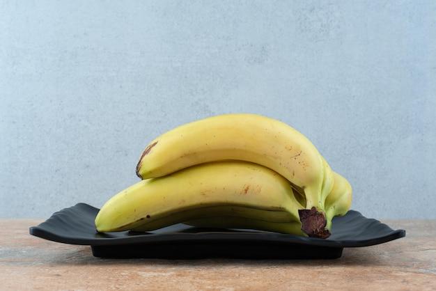 Темная тарелка, полная спелых фруктовых бананов на сером