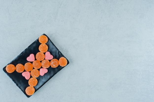 Темная тарелка, полная сладких апельсиновых желейных конфет с розовыми желейными конфетами в форме сердца.