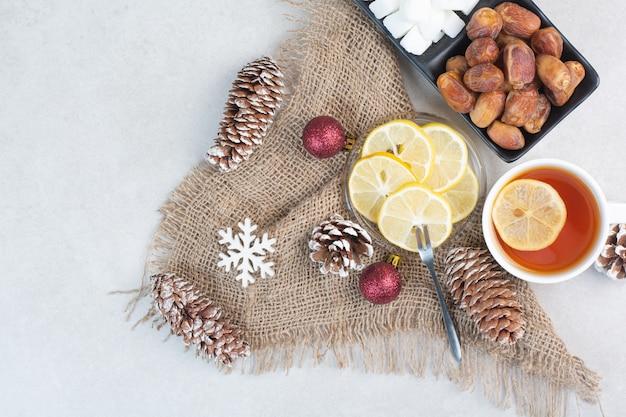 Темная тарелка буханки сахара и сухофруктов на белом фоне. фото высокого качества