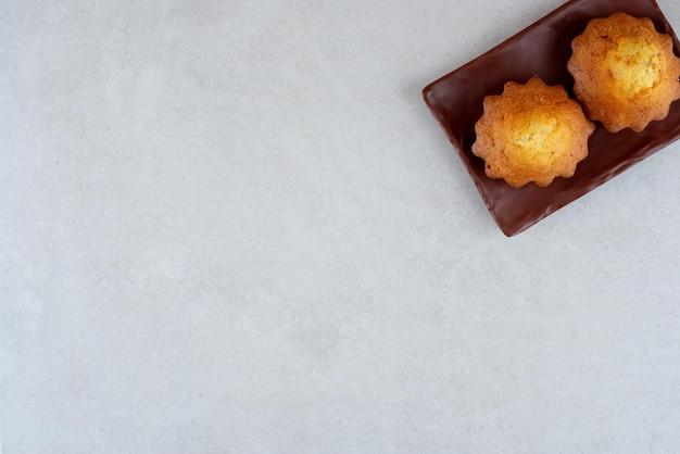 Темная тарелка двух вкусных кексов на белом столе.