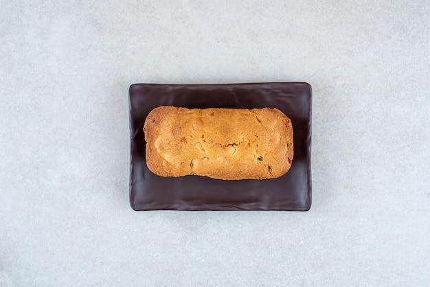 白いテーブルの上においしい新鮮なケーキと暗いプレート。