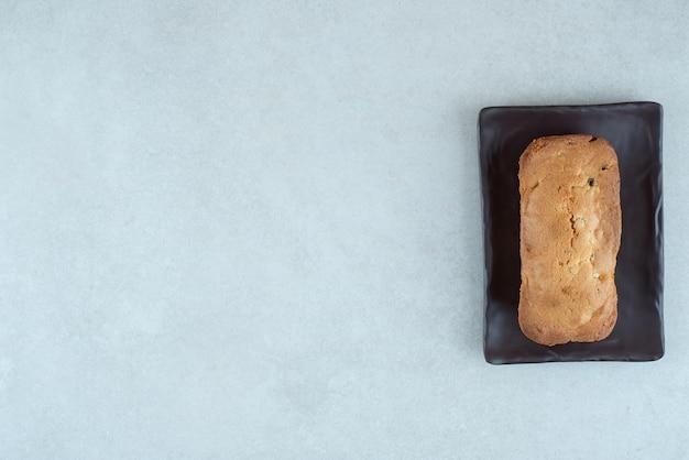 白地に美味しい焼きたてのケーキが入ったダークプレート
