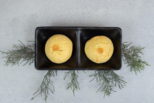 白い表面に2つの丸い甘いクッキーが付いた暗いプレート。